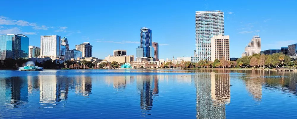 Skyline of tall buildings by water on sunny day in Downtown Orlando.