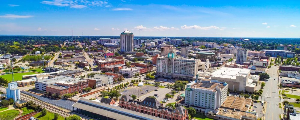 Skyline of buildings in Montgomery, AL on a sunny day.