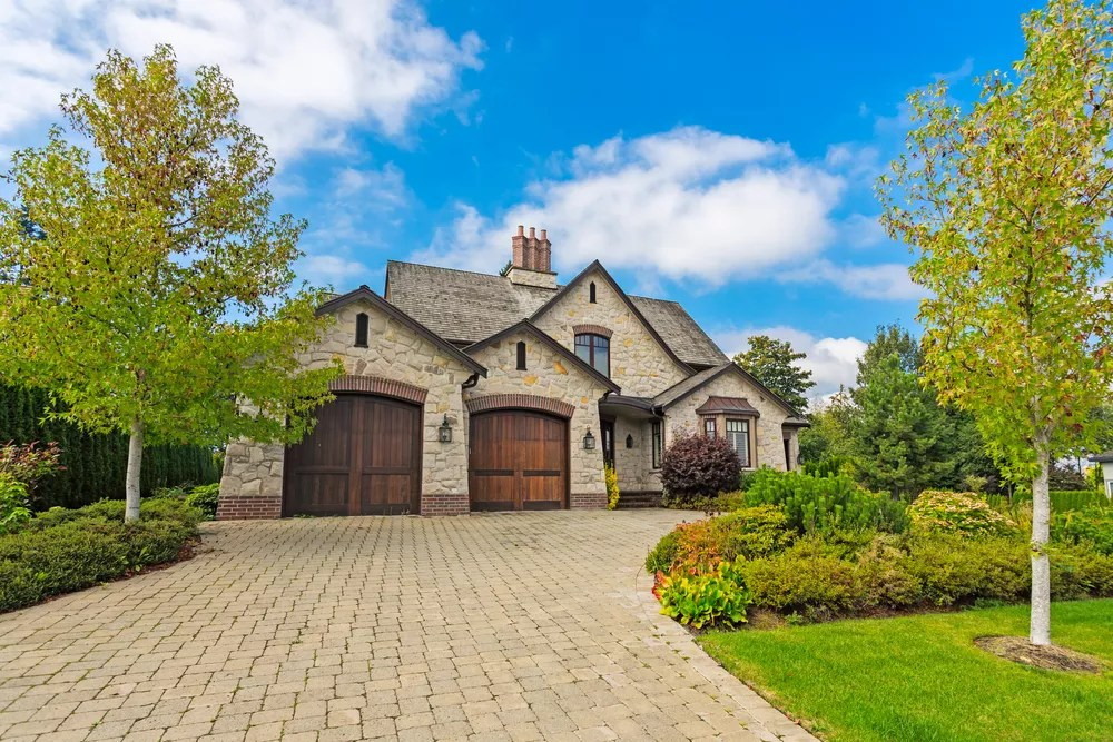 nice two home with brick laid driveway and nice landscaping