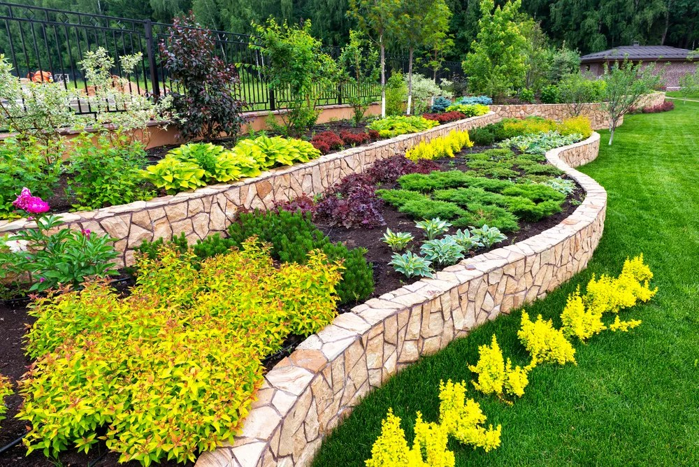 well landscaped backyard with multiple levels of tiered planting beds filled with foliage