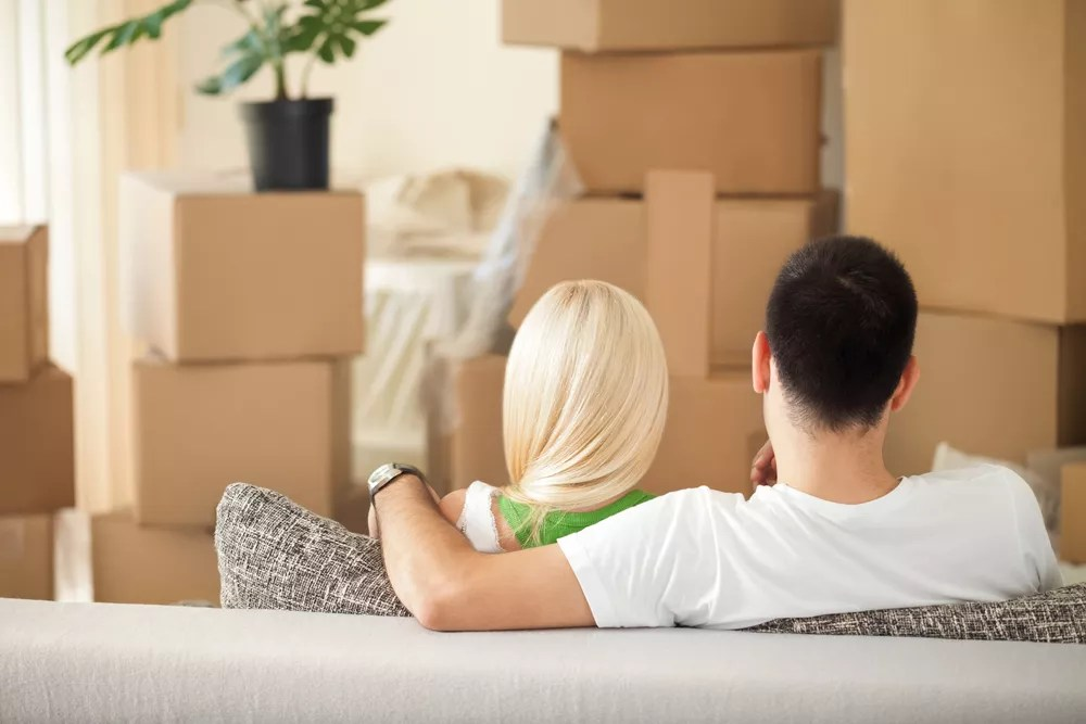 man and woman sitting on a couch in front of cardboard boxes
