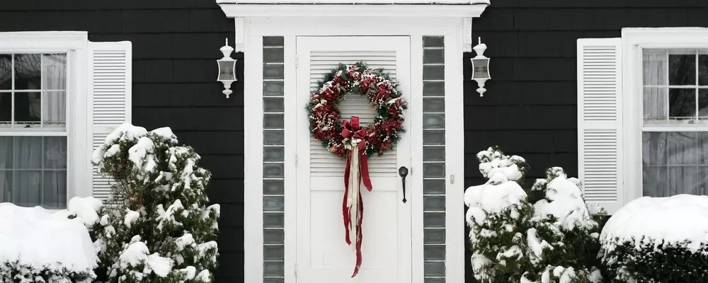 A white door with a traditional pine wreath and red and gold ornaments is hanged on a white door of a house surrounded by snow