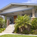 Bungalow-style home in San Diego with a palm plant in the front yard.