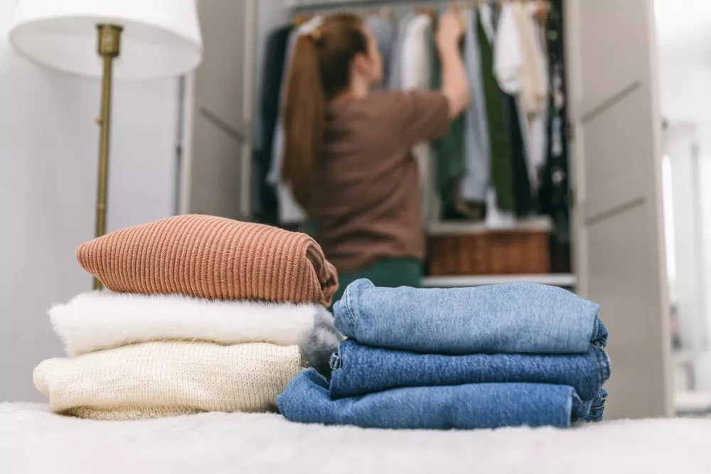 Woman Putting Clothes Away in a Closet with Folded Clothes on the bed