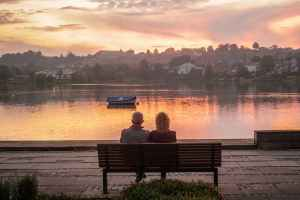A heterosexual couple sit on a bench overlooking a river and cityscape