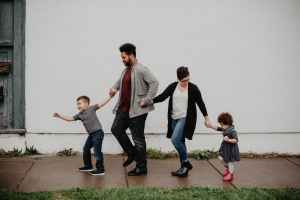 A young family of four walks together on a sidewalk