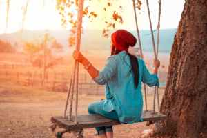 A woman sits on a wooden swing at sunset