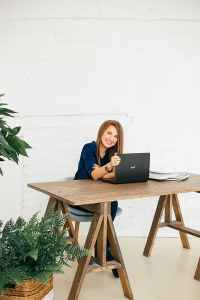 A woman sits at a wooden table with her laptop