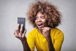 A woman looks at her phone with joyful surprise on her face
