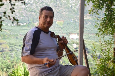 Kostis playing the lyra with the amazing background view of the area of Sisses