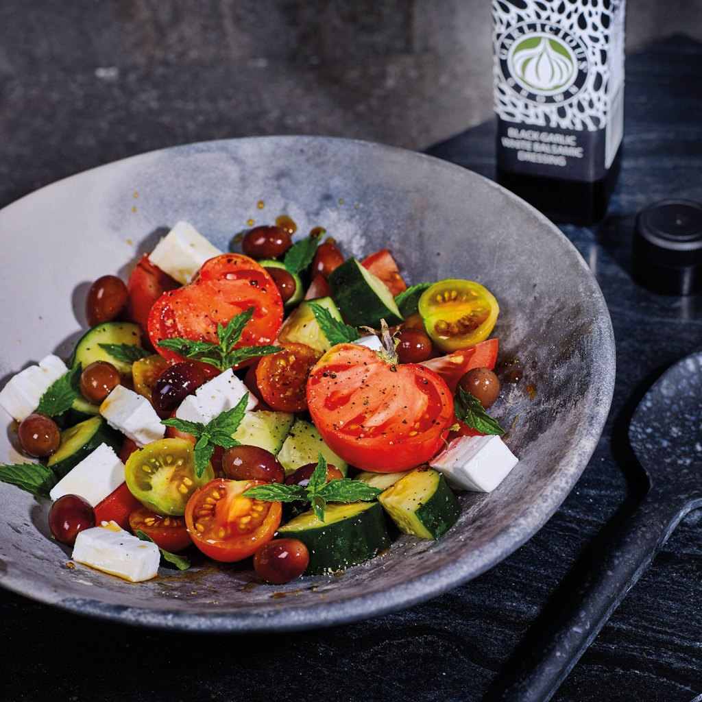 Vegan Greek Salad with a mix of heirloom and cherry tomatoes, vegan feta and Black Garlic White Balsamic Dressing