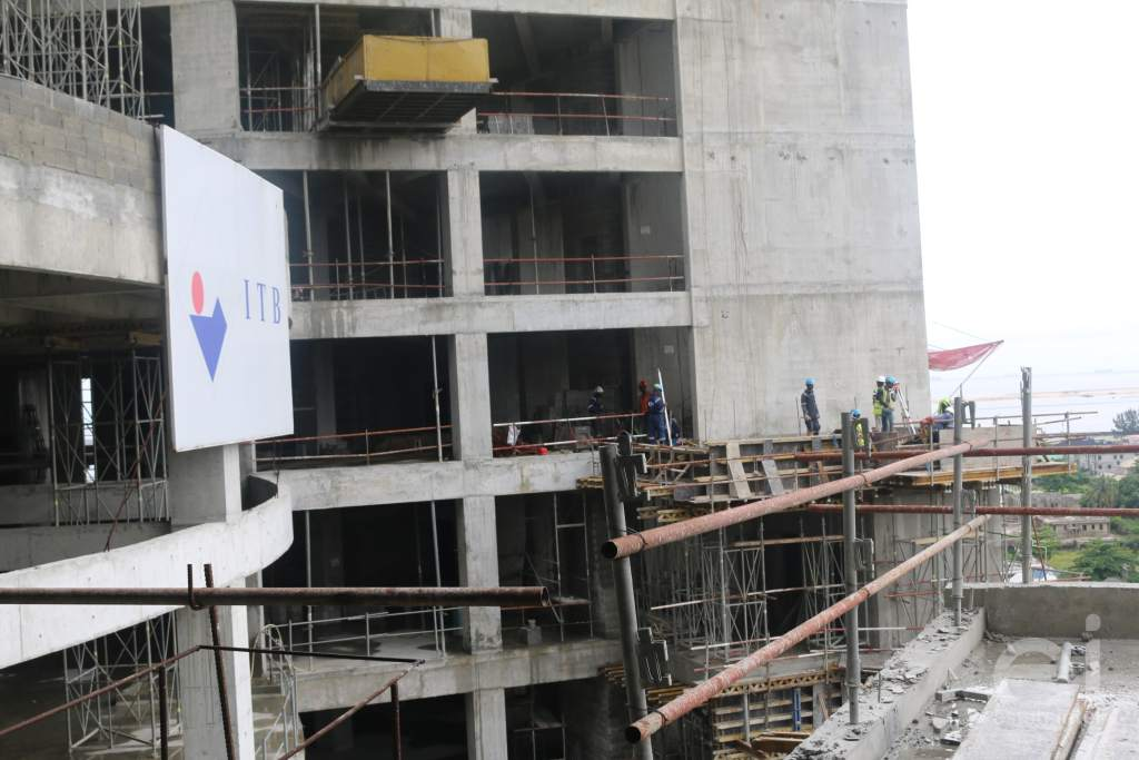 A board with ITB Construction Limited written on it with construction workers in a distance at Trinity Towers construction site