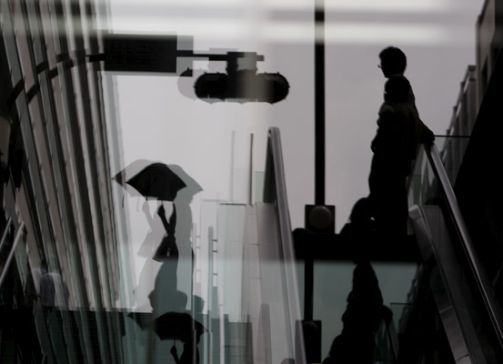 En esta instantánea se pueden apreciar unas personas bajando por unas escaleras mecánicas reflejadas en un cristal de un edificio de Tokio (Japón).