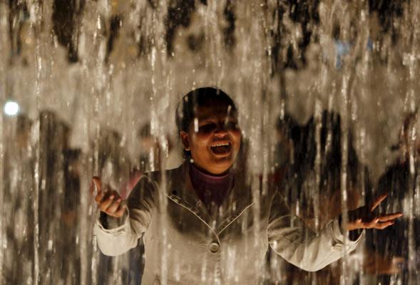 Una mujer juega dentro de una fuente de un parque de Lima (Perú).