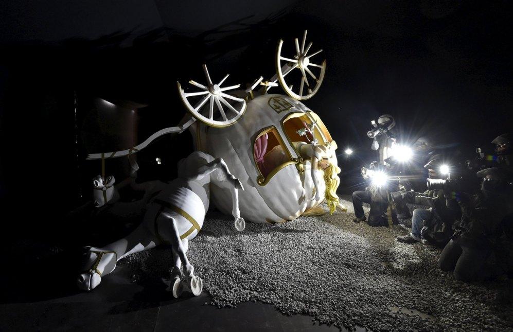 La carroza de Cenicienta, por los suelos, después de sufrir un accidente. La princesa parece muerta. Los fotógrafos, desplazados a la zona, toman fotografías.