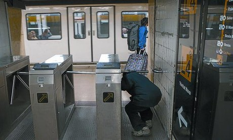 Un hombre pasa, sin validar billete alguno, por debajo de un torniquete de la estación de metro de Jaume I de la L-4, ayer.