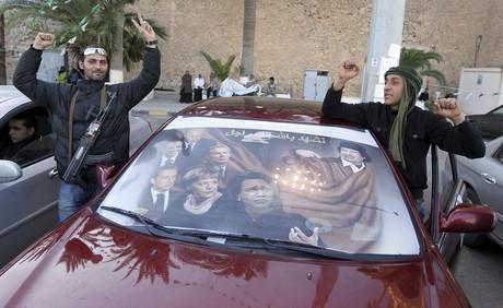 Dos partidarios de Muamar Gadafi hacen signos de victoria, el lunes, en Trípoli.