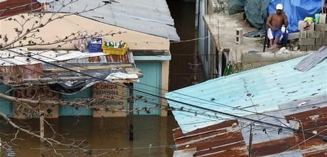 Un hombre permanece en el techo de su casa en un barrio de Santo Domingo, inundado por las lluvias de la tormenta, el lunes.