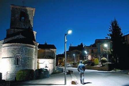 Un carrer de l'Estany, amb el monestir de Santa Maria, a l'esquerra, il·luminat per llums led.