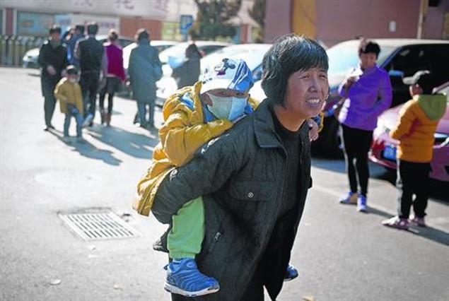 Una dona carrega el seu fill a l'esquena en un carrer de Pequín.