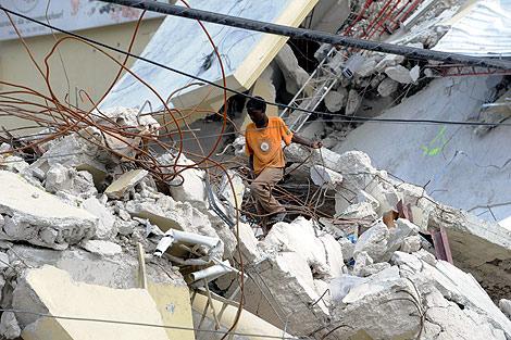 Un haitiano pasea entre los escombros de unas casas. | AFP