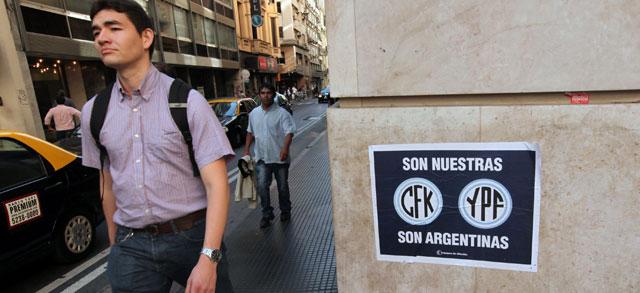 Un hombre pasa cerca de un cartel que reclama las petroleras como argentinas. | Efe