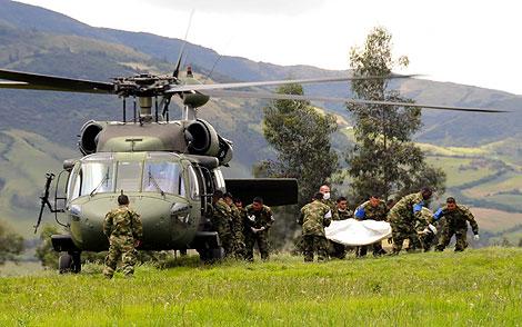 Soldados colombianos portan el cadáver de uno de sus compañeros. | Efe