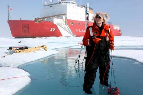 Una de las investigadoras, tomando muestras del agua con plantas en el Ártico.  NASA