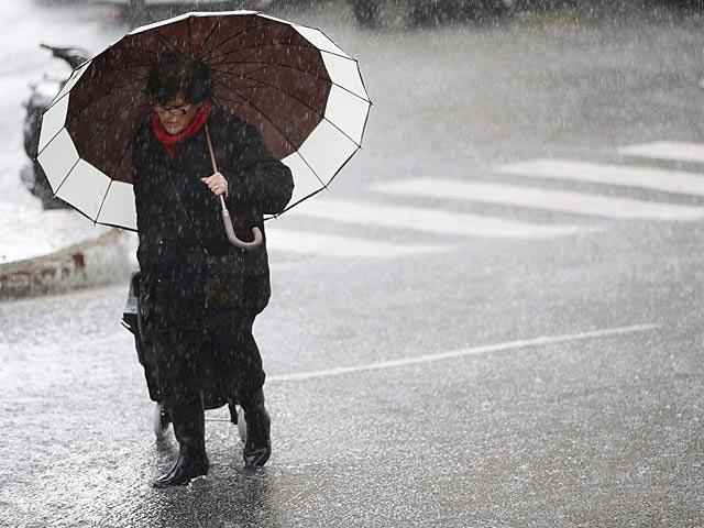 Una mujer se protege de la lluvia hoy en Marbella (Málaga). | Jorge Zapata / Efe