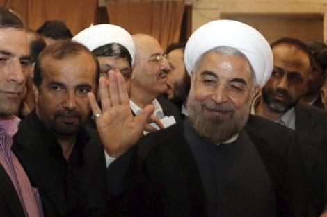 El candidato Hasan Rohani saluda en el momento de votar. | Efe