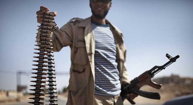 Un rebelde muestra un cinturón de balas ante la puerta oeste de la ciudad de Ghualish. | Afp