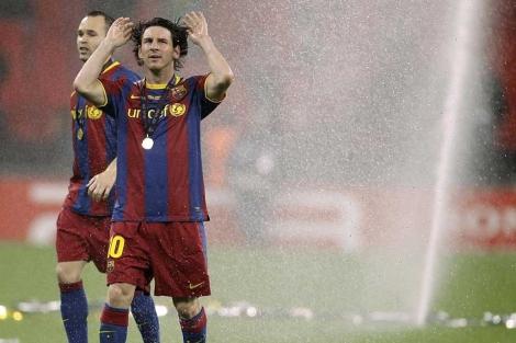 Messi, Iniesta y la lluvia de aspersores. (EFE)