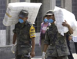 Dos soldados mexicanos llevan paquetes con máscaras para la población en la capital. | Reuters