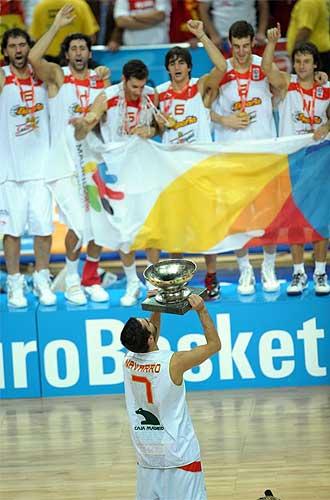 Navarro levanta la copa mientras los jugadores portan la pancarta en el podio.