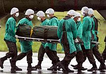 Varios soldados transporan uno de los cuerpos. | Efe