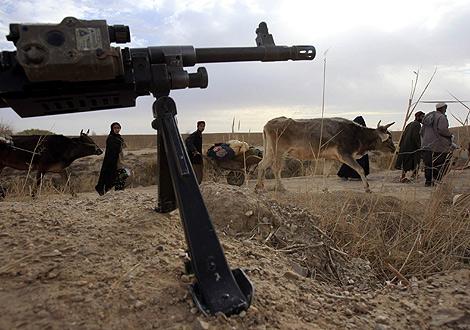 Varios afganos caminan frente al fusil de un soldado de la OTAN. | Reuters