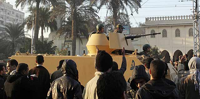 Egipcios rodean un tanque que protege el palacio presidencial de Mursi. / FOTO: Reuters