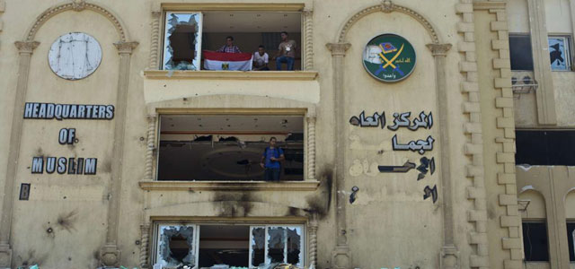 Opositores en la sede de los Hermanos Musulmanes en El Cairo, que ha sido incendiada. | Afp