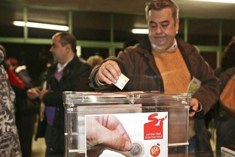 Un hombre realiza una donación solidaria.| Javier Gutiérrez