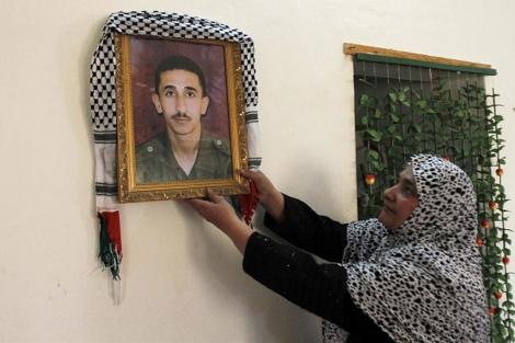 La madre de uno de los presos que serán liberados muestra su foto.| Reuters
