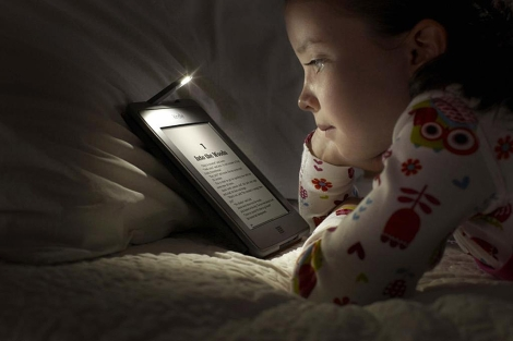 Una niña lee en un Kindle Touch de Amazon. | Efe