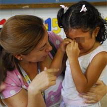 Una mujer habla con su hija para consolarla el primer día de clase.