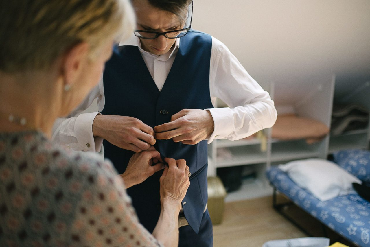 Le marié aidé par sa maman pour boutonner sa tenue