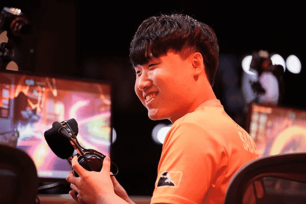 """Su-min """"SADO"""" Kim smiles, putting on his headset as he gets ready for a game in the Overwatch League"""