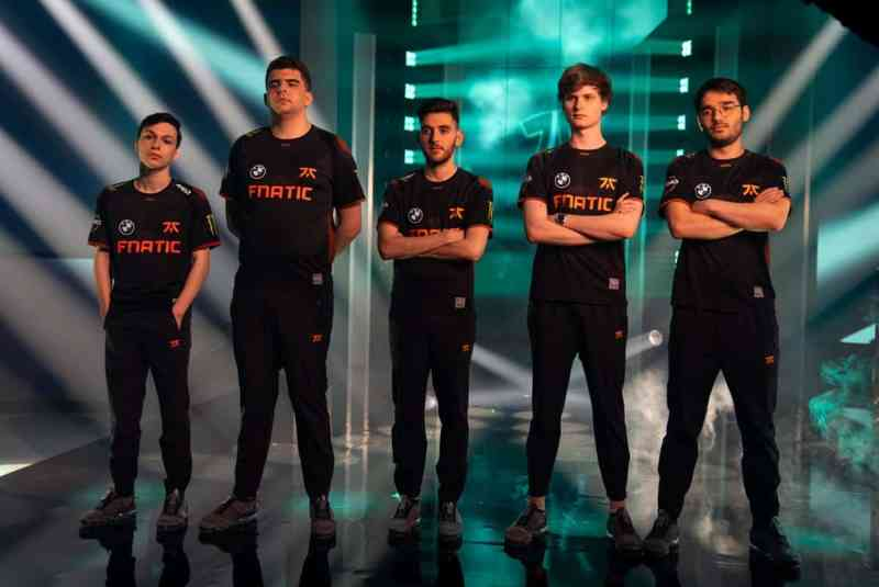 The Fnatic LEC team of Adam, Bwipo, Nisqy, Upset and Hylissang stand together with a bunch of spotlights behind them on the LEC stage.