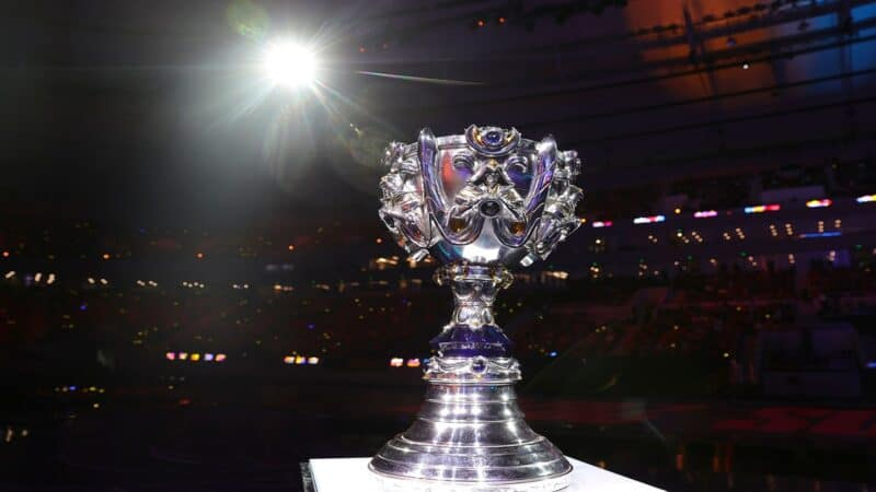 The Summoner's Cup from the LoL World Championship stands tall on a podium with a spotlight illuminating it.