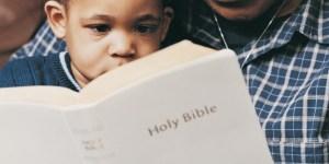 Padre e hijo leyendo la Biblia juntos.
