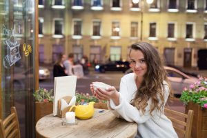 Single woman sitting at a cafe table holding a mug