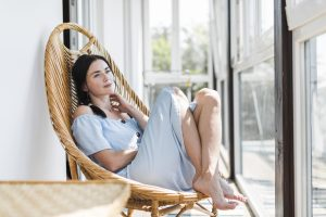 woman relaxing on a wicker chair