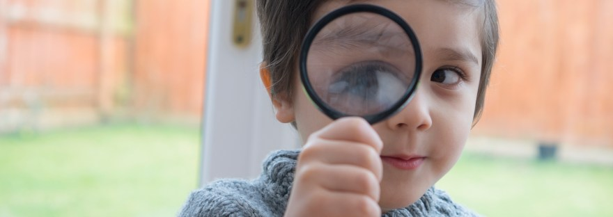 Boy holding a magnifying glass showing a big eye next to the door